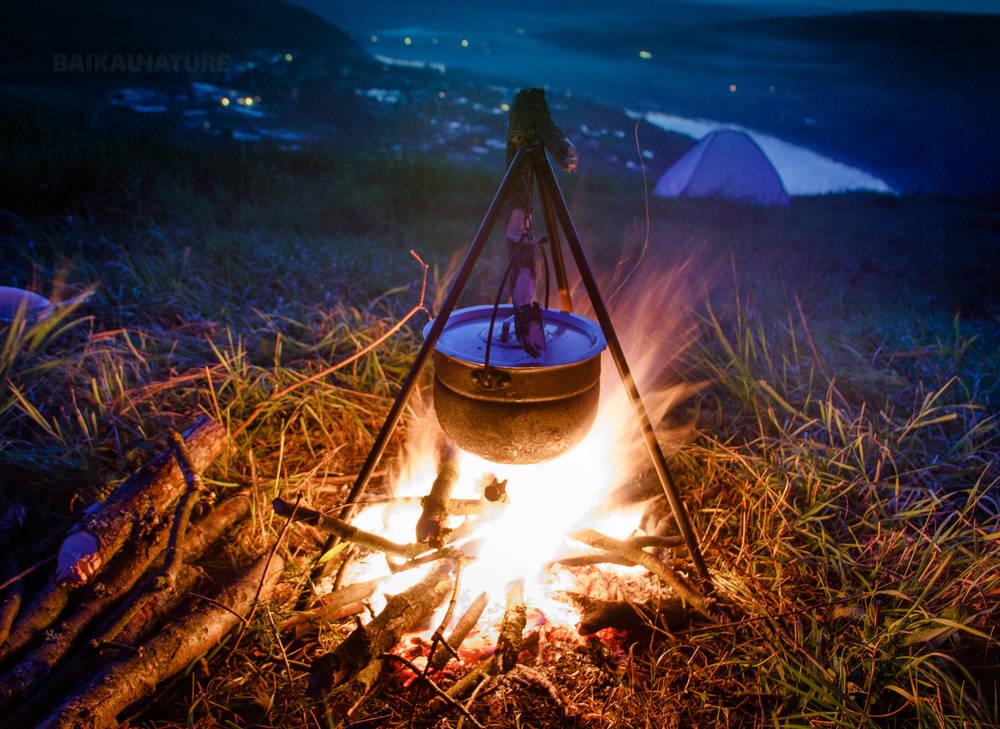 Кипящий котел у костра на пикнике после захода солнца. Приготовление пищи в полевых условиях.